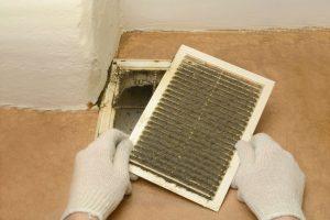 man removes dust ventilation grilles